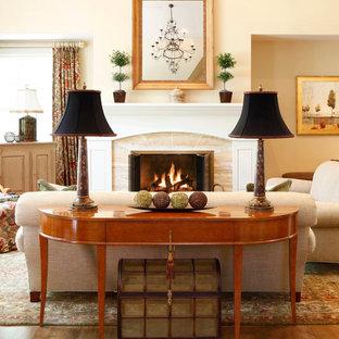 Diseño de sala de estar clásica, sin televisor, con paredes beige, suelo de madera en tonos medios y chimenea tradicional