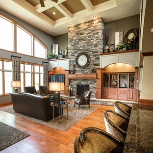 Inspiration for a large arts and crafts open concept family room in Other with grey walls, medium hardwood floors, a standard fireplace, a stone fireplace surround, a built-in media wall and brown floor.