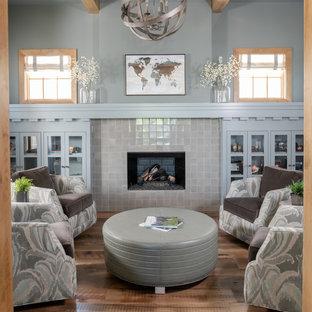 ダラスのトランジショナルスタイルのおしゃれなファミリールーム (青い壁、無垢フローリング、標準型暖炉、タイルの暖炉まわり、茶色い床) の写真