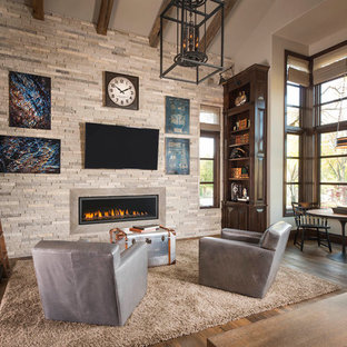 Example of a tuscan enclosed dark wood floor and brown floor family room design in Dallas with beige walls, a ribbon fireplace and a stone fireplace