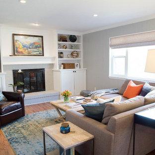 デンバーの中サイズのコンテンポラリースタイルのおしゃれなファミリールーム (グレーの壁、無垢フローリング、標準型暖炉、レンガの暖炉まわり、埋込式メディアウォール) の写真
