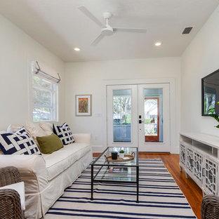 Ejemplo de sala de estar cerrada, marinera, con paredes blancas, suelo de madera en tonos medios, televisor colgado en la pared y suelo marrón