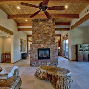 Imagen de sala de estar abierta, de estilo de casa de campo, con suelo de piedra caliza, chimenea de doble cara, marco de chimenea de piedra y suelo blanco