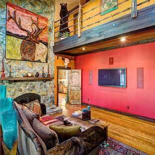 Foto di un soggiorno stile americano aperto con libreria, pareti rosse, parquet chiaro, camino classico, cornice del camino in pietra, parete attrezzata e pavimento marrone