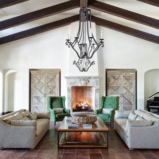 Idées déco pour une grande salle de séjour méditerranéenne avec un mur blanc, un sol en carreau de terre cuite, une cheminée standard et un sol marron.