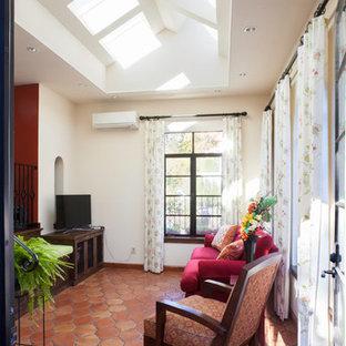 Esempio di un soggiorno mediterraneo di medie dimensioni e aperto con nessun camino, pareti bianche, pavimento in terracotta, TV autoportante e pavimento arancione