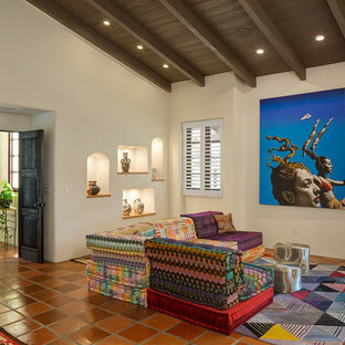 Inspiration for a southwestern terra-cotta tile and red floor family room remodel in San Diego with beige walls