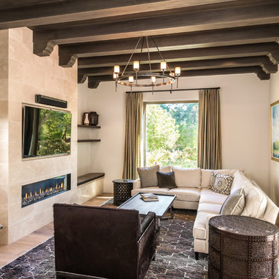 Family room - mediterranean open concept light wood floor and beige floor family room idea in San Francisco with beige walls, a ribbon fireplace, a stone fireplace and a wall-mounted tv