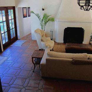 Foto de sala de estar cerrada, mediterránea, de tamaño medio, con paredes blancas, suelo de baldosas de terracota, chimenea tradicional, marco de chimenea de hormigón y suelo rojo