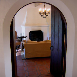 Example of a mid-sized tuscan enclosed terra-cotta floor and red floor family room design in Santa Barbara with white walls, a standard fireplace and a concrete fireplace