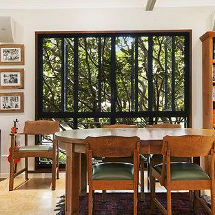 Idee per un soggiorno tropicale di medie dimensioni e chiuso con libreria, pareti beige, pavimento in compensato, nessuna TV e pavimento marrone