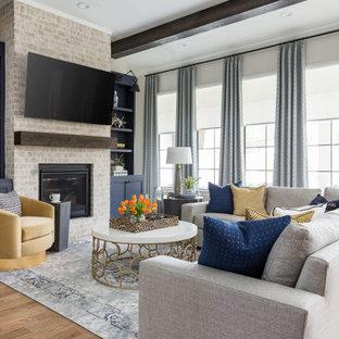 Klassisches Wohnzimmer mit weißer Wandfarbe, braunem Holzboden, Kamin, Kaminumrandung aus Stein, braunem Boden und freigelegten Dachbalken in Houston