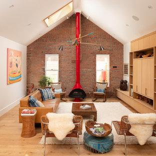 Ejemplo de sala de estar abierta, retro, con paredes blancas, suelo de madera clara, estufa de leña y televisor retractable