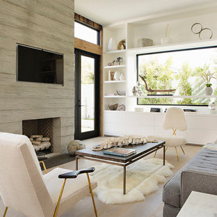 Inspiration for a contemporary light wood floor and beige floor family room remodel in Orange County with a standard fireplace, a wood fireplace surround and a wall-mounted tv