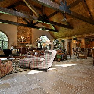 Esempio di un ampio soggiorno tradizionale aperto con pareti beige, pavimento in travertino, camino classico e cornice del camino in pietra
