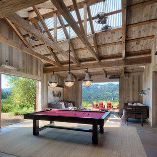 Immagine di un ampio soggiorno in campagna chiuso con sala giochi, pareti grigie, pavimento in cemento, TV nascosta e pavimento marrone