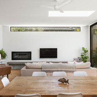 メルボルンの広いコンテンポラリースタイルのおしゃれなオープンリビング (白い壁、淡色無垢フローリング、コーナー設置型暖炉、金属の暖炉まわり、壁掛け型テレビ) の写真