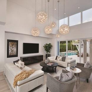 Ejemplo de sala de estar actual con paredes blancas, suelo de madera clara y televisor colgado en la pared