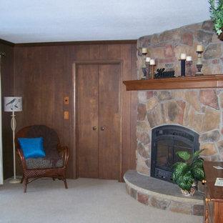 Modelo de sala de estar con biblioteca cerrada, tradicional, pequeña, sin televisor, con paredes marrones, moqueta, chimenea de esquina y marco de chimenea de piedra