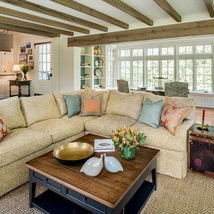 Imagen de sala de estar con biblioteca abierta, campestre, grande, sin televisor, con paredes beige, suelo de madera en tonos medios, suelo marrón, chimenea tradicional y marco de chimenea de piedra