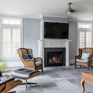 ニューヨークの大きいトラディショナルスタイルのおしゃれなファミリールーム (グレーの壁、スレートの床、標準型暖炉、石材の暖炉まわり、壁掛け型テレビ) の写真