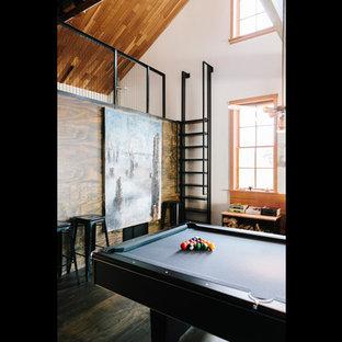 Aménagement d'une grande salle de séjour mansardée ou avec mezzanine industrielle avec salle de jeu, un mur blanc et un sol en contreplaqué.