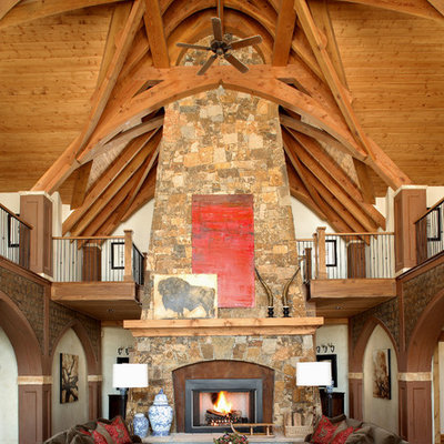 Family room - rustic open concept dark wood floor family room idea in Denver with beige walls, a standard fireplace and a stone fireplace