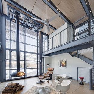 Foto di un piccolo soggiorno industriale chiuso con pareti bianche, pavimento in cemento e camino sospeso