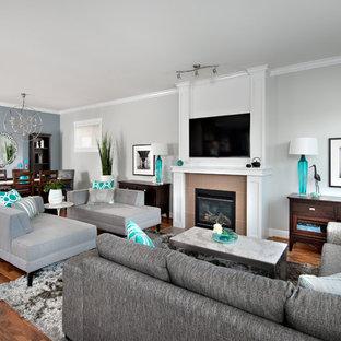 Modelo de sala de estar abierta, contemporánea, con suelo de madera en tonos medios, chimenea tradicional, marco de chimenea de baldosas y/o azulejos, televisor colgado en la pared y paredes multicolor