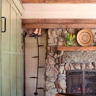 Foto de sala de estar abierta, rural, pequeña, con suelo de madera en tonos medios, chimenea tradicional y marco de chimenea de piedra