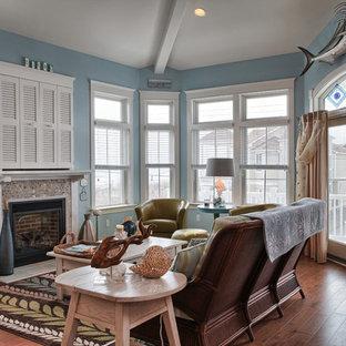 他の地域のビーチスタイルのおしゃれなファミリールーム (青い壁、内蔵型テレビ、タイルの暖炉まわり) の写真