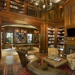 Réalisation d'une grande salle de séjour avec une bibliothèque ou un coin lecture tradition ouverte avec un sol en bois foncé, un téléviseur encastré, un mur marron, une cheminée standard, un manteau de cheminée en pierre et un sol marron.