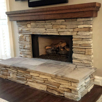 Inspiration for a rustic dark wood floor and brown floor family room remodel in Atlanta with a standard fireplace, a stone fireplace, beige walls and a wall-mounted tv