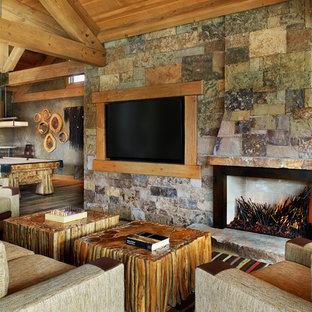 Immagine di un ampio soggiorno rustico aperto con sala giochi, pareti multicolore, pavimento in legno massello medio, camino classico, cornice del camino in pietra e parete attrezzata