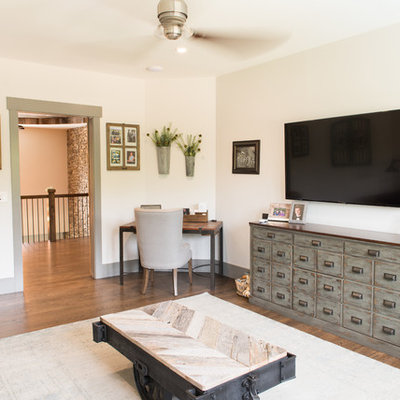 Inspiration for a mid-sized rustic enclosed dark wood floor and brown floor family room remodel in Charleston with beige walls, no fireplace and a wall-mounted tv