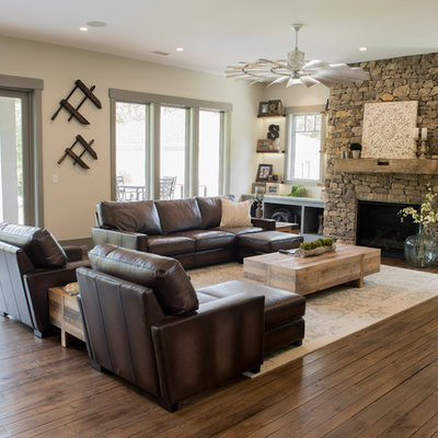 Large mountain style open concept dark wood floor and brown floor family room photo in Charleston with beige walls, a standard fireplace, a stone fireplace and a wall-mounted tv