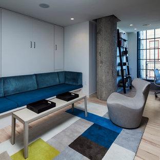 Imagen de sala de estar cerrada, urbana, de tamaño medio, con paredes grises, suelo de madera clara y televisor retractable