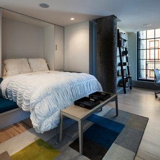 Idee per un soggiorno industriale di medie dimensioni e chiuso con pareti grigie, parquet chiaro e TV nascosta