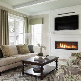リッチモンドのトラディショナルスタイルのおしゃれなファミリールーム (ベージュの壁、無垢フローリング、横長型暖炉、木材の暖炉まわり、壁掛け型テレビ、茶色い床) の写真