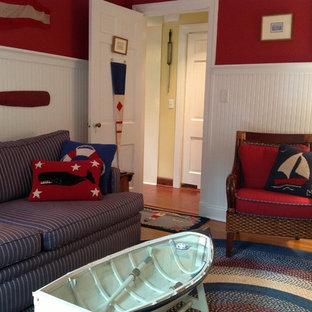 Kleines, Fernseherloses, Abgetrenntes Maritimes Wohnzimmer ohne Kamin mit roter Wandfarbe, braunem Holzboden und braunem Boden in New York