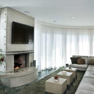 サンディエゴの大きいビーチスタイルのおしゃれな独立型ファミリールーム (ホームバー、白い壁、スレートの床、両方向型暖炉、コンクリートの暖炉まわり、壁掛け型テレビ) の写真