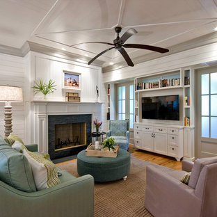 Family room - traditional medium tone wood floor family room idea in Charleston with white walls, a standard fireplace and a wall-mounted tv