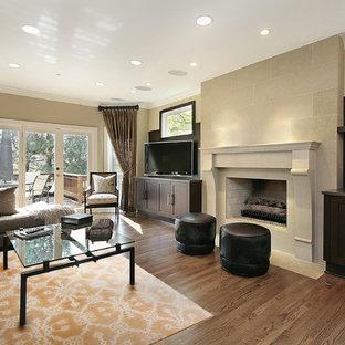 Immagine di un soggiorno chic di medie dimensioni con pareti beige, pavimento in legno massello medio, camino classico, cornice del camino in cemento e porta TV ad angolo