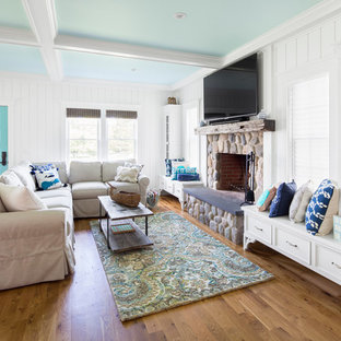 ボストンの大きいビーチスタイルのおしゃれなファミリールーム (白い壁、無垢フローリング、標準型暖炉、石材の暖炉まわり、壁掛け型テレビ、茶色い床) の写真