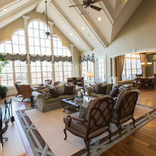 Inspiration for a mid-sized transitional open concept medium tone wood floor family room remodel in Raleigh with beige walls, a standard fireplace, a plaster fireplace and a wall-mounted tv