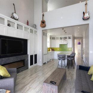 Esempio di un soggiorno stile marinaro di medie dimensioni e aperto con pareti bianche, pavimento in vinile, camino sospeso, cornice del camino in cemento, parete attrezzata, pavimento grigio e soffitto in perlinato