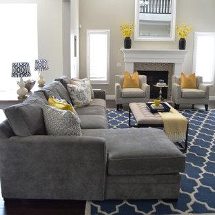 Cette photo montre une salle de séjour chic de taille moyenne et ouverte avec un téléviseur fixé au mur, un mur gris, un sol en bois foncé, une cheminée standard et un manteau de cheminée en carrelage.