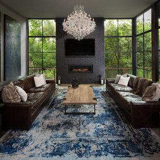 Diseño de sala de estar abierta, industrial, grande, con paredes grises, suelo de cemento, chimenea lineal, marco de chimenea de ladrillo, televisor colgado en la pared y suelo gris