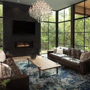 Réalisation d'une grand salle de séjour design ouverte avec un mur gris, béton au sol, une cheminée ribbon, un manteau de cheminée en brique et un téléviseur fixé au mur.