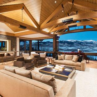 Réalisation d'une très grande salle de séjour minimaliste ouverte avec un bar de salon, un mur beige, un sol en bois clair, une cheminée standard, un manteau de cheminée en pierre, un téléviseur encastré et un sol marron.